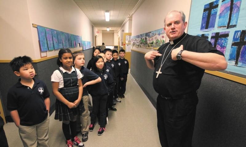 Auxiliary Bishop Peter L. Smith of Portland, Ore., speaks with students at St. Rose School in Portland March 19. He was born in Pietermaritzburg, South Africa, and went through a 13-year process to become a U.S. citizen. (CNS photo/Ed Langlois, Catholic Sentinel)
