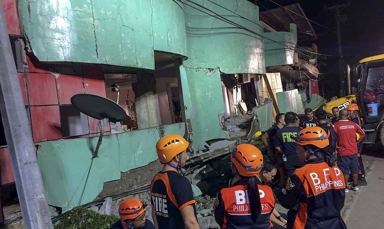 Rescuers view a damaged building following an earthquake July 6 in the Philippine province of Leyte. A week after the magnitude 6.5 earthquake hit the province, hundreds of residents continue to live in temporary shelters. (CNS photo/Ahyeng Gauit, EPA)