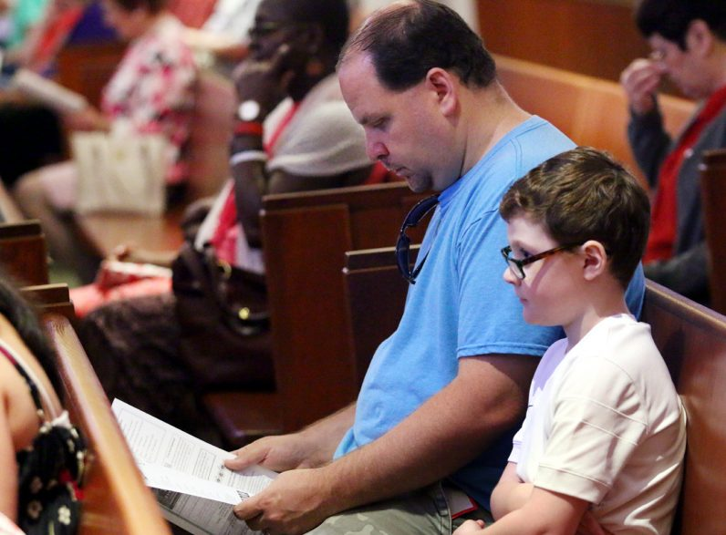 Jack Lanzalotti, right, attends Mass with his father Michael.