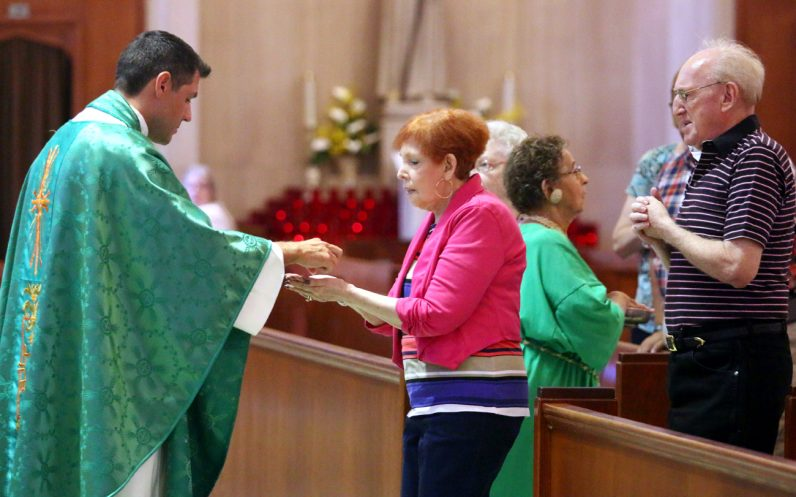 Father Jim DeGrassa distributes holy Communion to parishioners at Resurrection of Our Lord Church in Northeast Philadelphia.