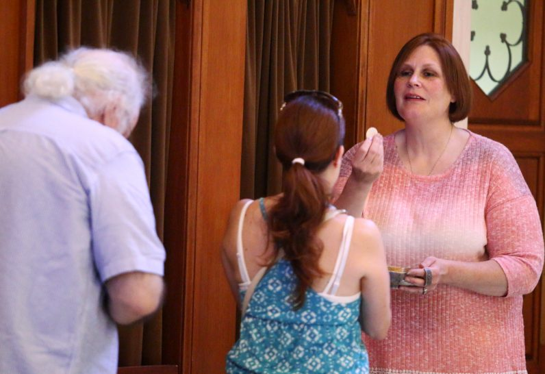Marianne Patterson distributes holy Communion.