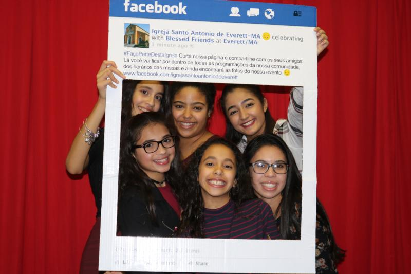 Young people from St. Anthony of Padua Parish in Everett, Mass., pose with a Facebook frame promoting their parish's Facebook page. The parish is home to the second-largest community of Brazilian Catholics in the Archdiocese of Boston. (CNS photo/courtesy St. Anthony of Padua Parish Facebook page)
