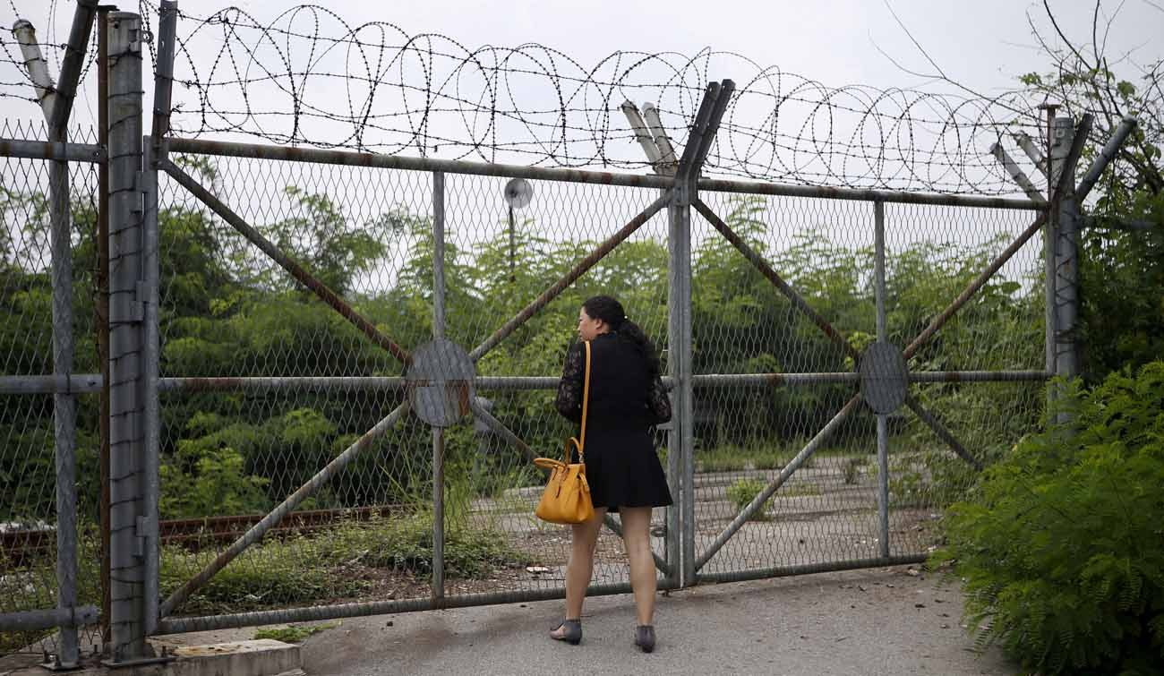 A Chinese tourist looks over a barbed-wire fence near the demilitarized zone that separates the two Koreas in Paju, South Korea, in this 2015 file photo. (CNS photo/Kim Hong-Ji, Reuters)