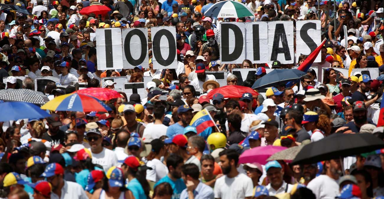 """Opposition supporters hold letters to build a banner that reads """"100 days"""" during a July 9 protest against Venezuelan President Nicolas Maduro's government in Caracas. (CNS photo/Carlos Garcia Rawlins, Reuters)"""