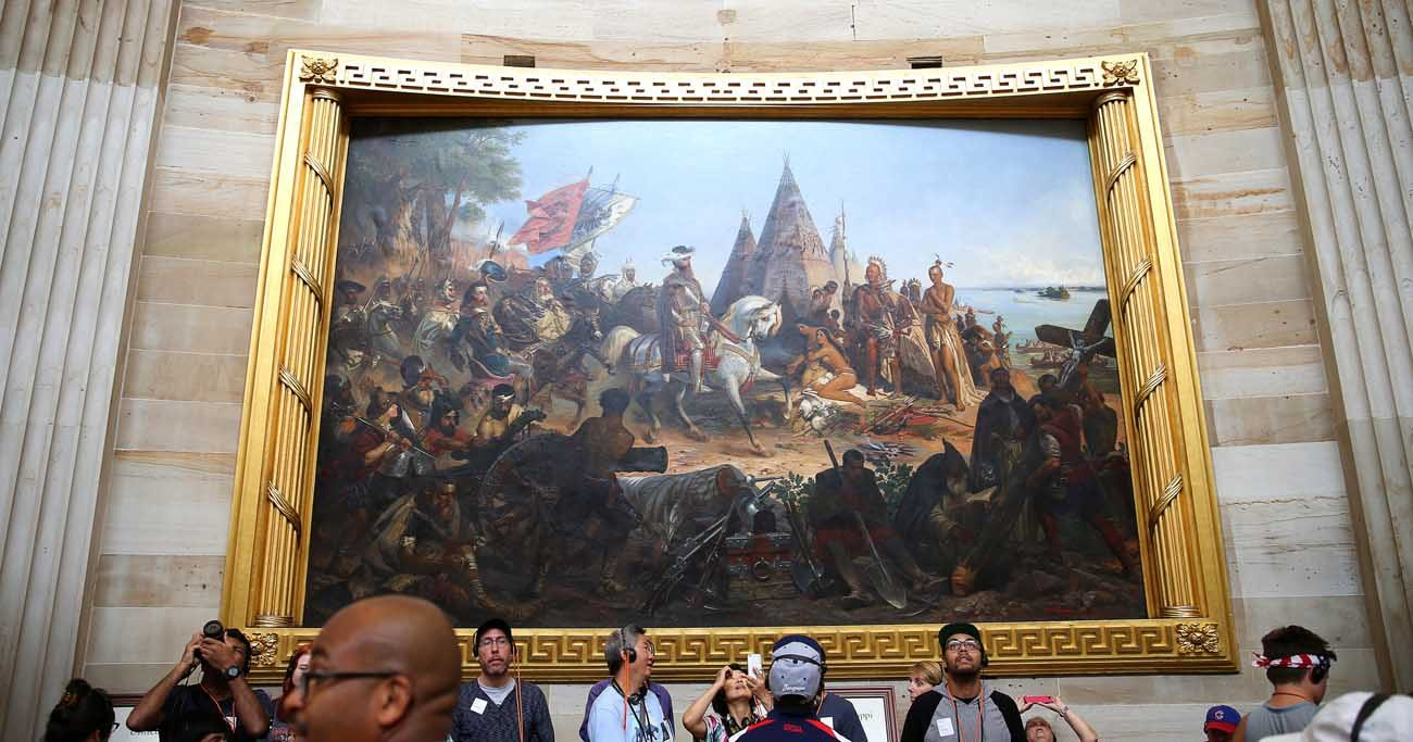 """A painting of the """"Discovery of the Mississippi"""" is seen at the U.S. Capitol in Washington July 6. The artwork depicts Hernando de Soto, a Spanish explorer, standing at the Mississippi River with priests, praying and placing a crucifix in the ground. (CNS photo/Tyler Orsburn)"""