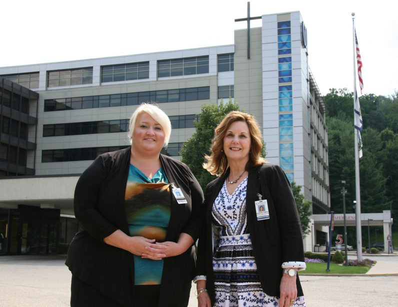 Heidi Porter, vice president of quality and regulatory affairs at Catholic-run Wheeling Hospital, and Kareen Simon, vice president of operations, pose for a photo outside the West Virginia hospital July 19. (CNS photo/Colleen Rowan, The Catholic Spirit)