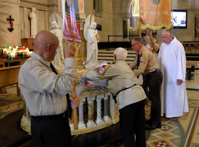 Leonard DiVittorio of the New York borough of Queens, third from left, leaves flowers at the statue of St. Anne July 25 in the Basilica of Ste.-Anne-de-Beaupre in Quebec. (CNS photo/Philippe Vaillancourt, Presence)