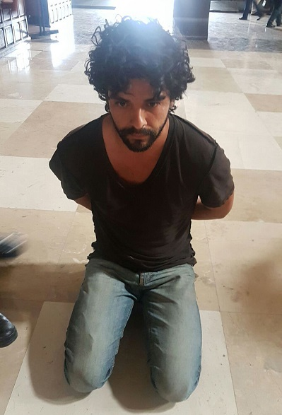 John Rock Schild is seen handcuffed after being accused of stabbing Father Miguel Angel Machorro three times during Mass May 15 at the Metropolitan Cathedral in Mexico City. Cardinal Norberto Rivera Carrera and the Metropolitan Cathedral said Aug. 3 that Father Machorro has died. (CNS photo/EPA)