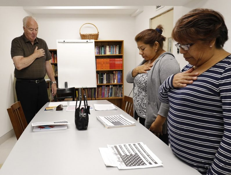 Volunteer instructor Jack Carroll and students recite the pledge of allegiance in October 2016 during a class at St. Luke Church in Brentwood, N.Y., for immigrants who are preparing to apply for U.S. citizenship. (CNS photo/Gregory A. Shemitz)