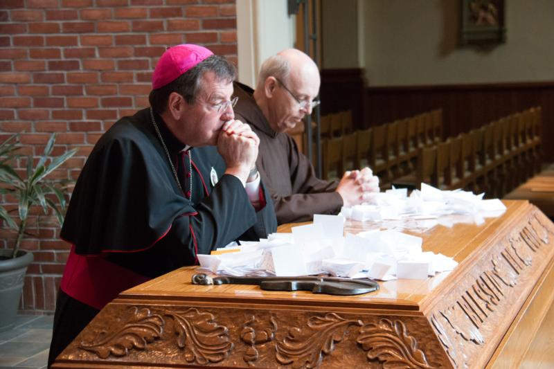 Detroit Archbishop Allen H. Vigneron and Capuchin Father Michael Sullivan pray May 4 at the tomb of Father Solanus Casey before the announcement of the friar's beatification at St. Bonaventure Monastery in Detroit. (CNS photo/courtesy Archdiocese of Detroit)