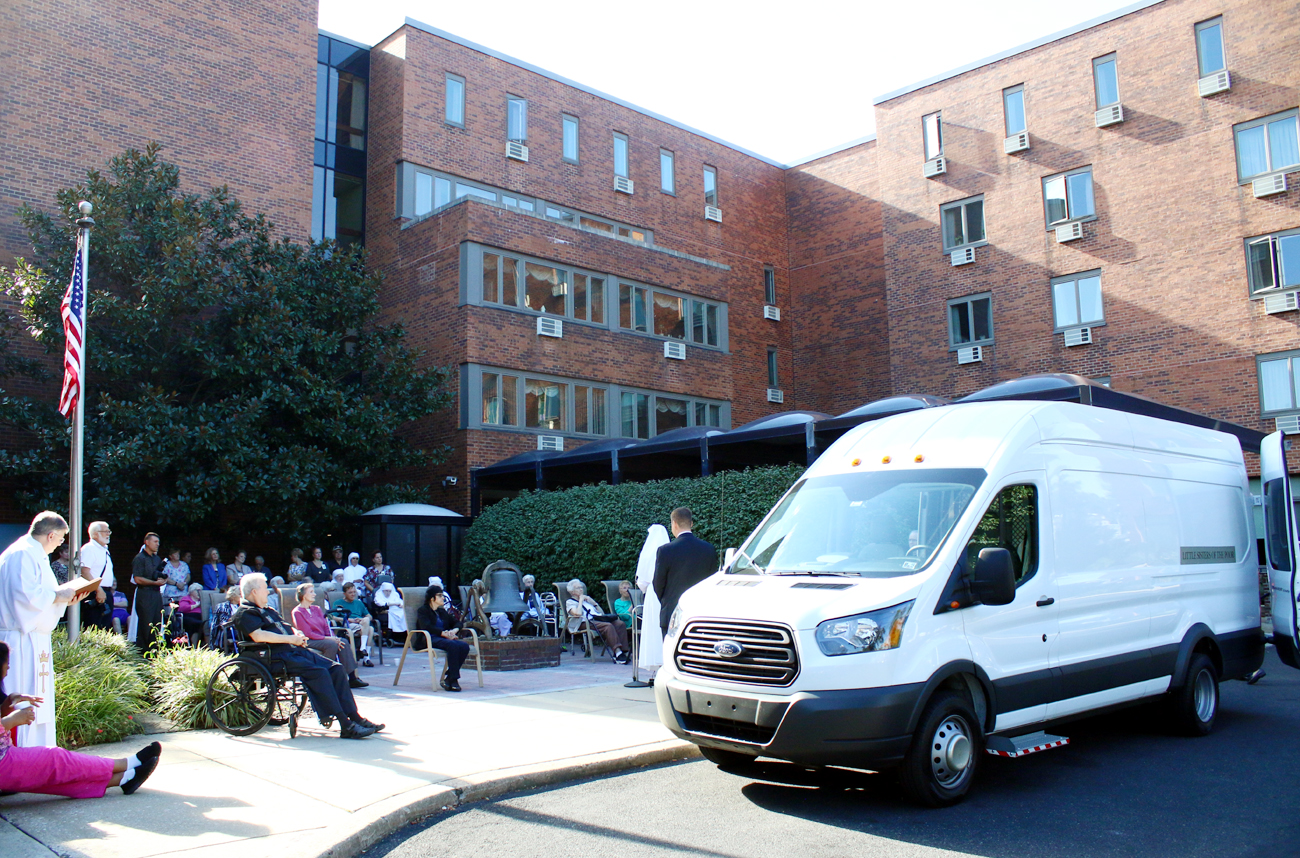 Residents of Holy Family Home in Southwest Philadelphia and guests gather for the blessing of the new van Oct. 6 by the home's chaplain, Father James Sullivan, at far left.