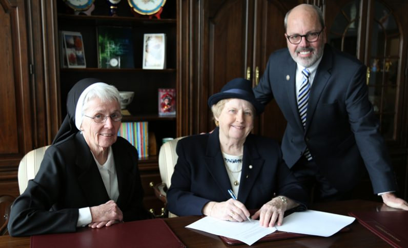 ... Harrington (center) signs over a property donation valued at $350,000 to Holy Family University, making it one of the university's largest single gifts ...