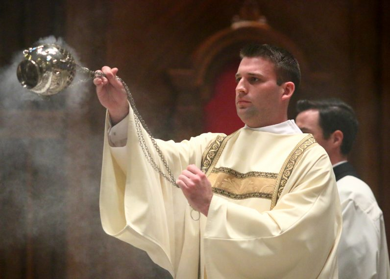 Rev. Mr. Kyle Adamczyk blesses the congregation with incense during the Chrism Mass March 29 at the Cathedral Basilica of SS. Peter and Paul.