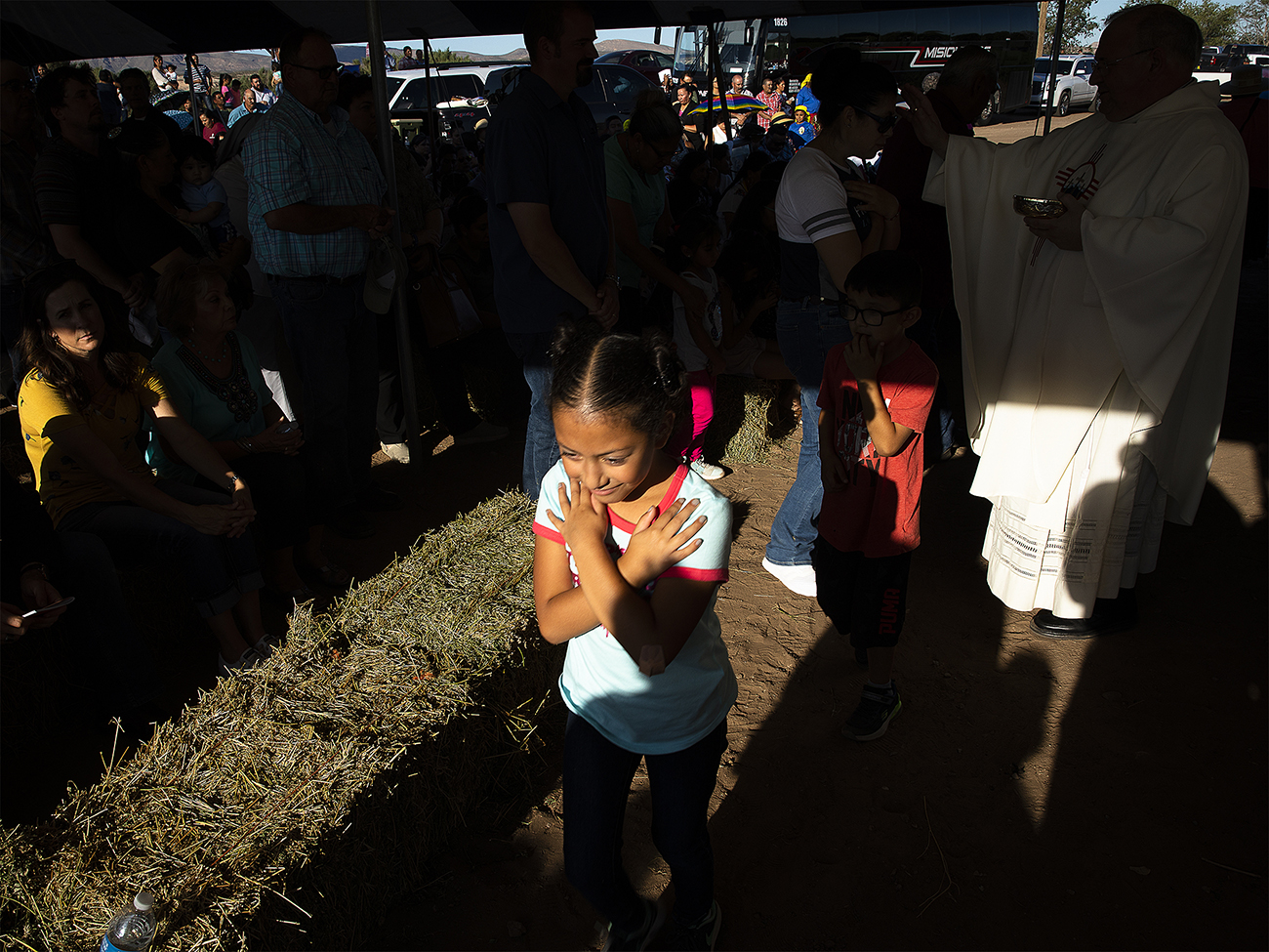 A girl crosses her arms after receiving a blessing during Communion at an outdoor Mass Sept. 26, 2019, in Hatch, N.M., which was part of a pastoral encounter by U.S. bishops with migrants at the border. The Sept. 23-27 pastoral visit, sponsored by various offices of the U.S. Conference of Catholic Bishops and other national organizations, aimed to highlight the church's ministry to migrants, the border conditions and immigration laws affecting them, and their material and spiritual needs. (CNS photo/Tyler Orsburn)