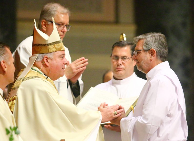 Deacon Franz N. Fruehwald right) makes the promise of the elect to Archbishop Nelson Perez during the diaconate ordination Mass June 13.