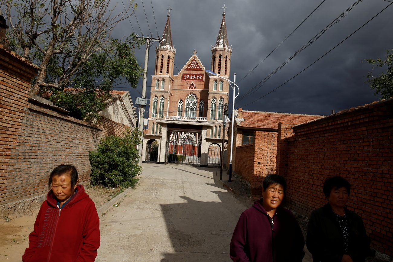 Villagers are pictured in a 2018 photo walking near a Catholic church in Huangtugang, China. Cardinal Pietro Parolin, Vatican secretary of state, spoke about divisions in the church, the Vatican's approach to China and other issues in an interview that aired April 5, 2021, on Spain's COPE radio network, which aired April 5, 2021.